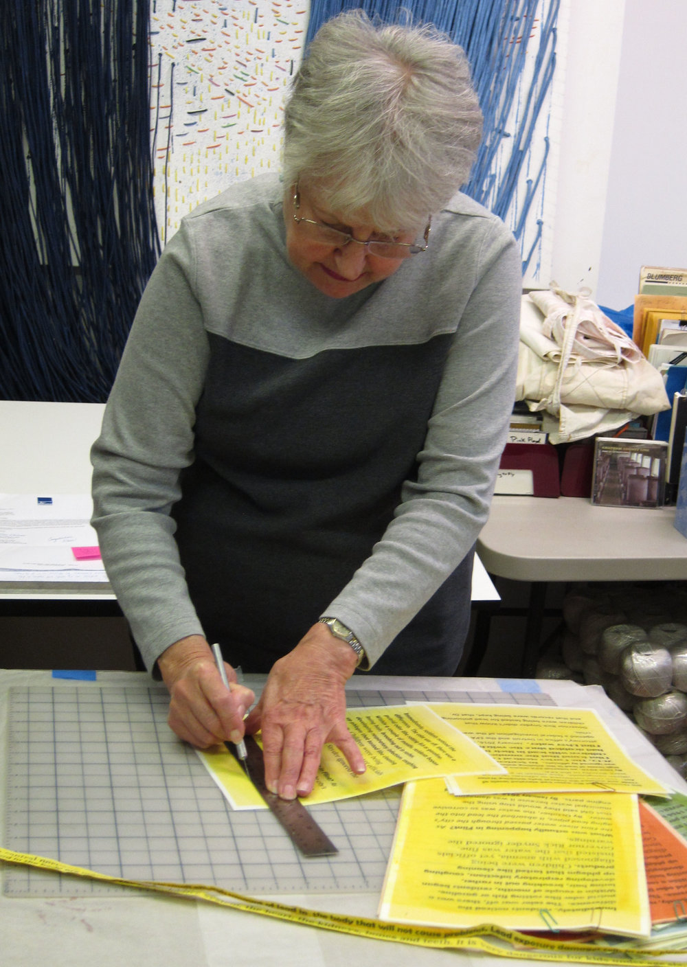 Elaine Longtemps cutting fabric strips for new work.