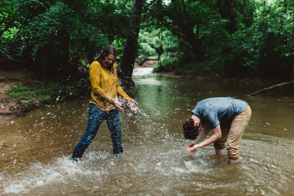 Engagement portrait of Maryland couple playing outside in a puddle.
