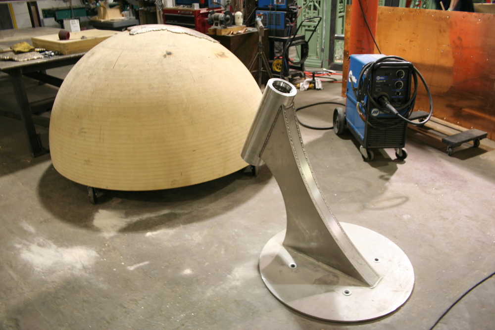 The base was laser cut out of stainless steel, and then formed and welded. There is another smaller element at the top of the globe.
