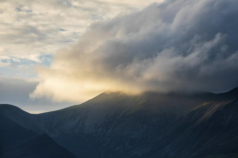 Lake District (England)  Als reis- en landschapsfotograaf stond het Lake District al een tijdje op mijn lijstje. Het hotel dat ik boekte in Keswick is zo'n heerlijk oud Engels huis, gebouwd in 1810 (als ik het goed begrepen heb van de eigenaar) en op loopafstand van het meer Derwent Water. Ideaal om op mijn eerste avond een zonsondergang te gaan fotograferen. De zon ging die avond om kwart voor tien onder en een uur daarvoor had ik een mooie steiger gevonden om te fotograferen. Tijdens het fotograferen met mijn groothoeklens zag ik plotseling rechts van mij dat het licht heel mooi op een berg viel. Snel wisselde ik van lens en met mijn telelens was ik precies op tijd om dit nog vast te leggen.