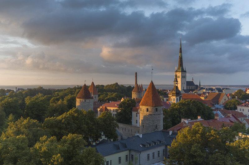 Tallinn - Estonia  In steden is het niet altijd makkelijk om unieke locaties te vinden met mooie uitzichten. Dit is dan ook een veel gefotografeerd plekje. Ik had geluk, want vlak voordat de laagstaande zon achter de bewolking verdween. Viel het licht nog één keer mooi op de Sint Olaf church. Bekijk   hier   ook de video over deze foto.