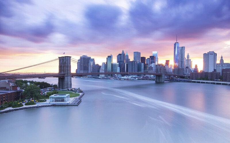 Brooklyn Bridge - New York  Een van de mooiste uitzichten op de skyline van NYC heb je vanaf de Manhattan Bridge. Door de hoge hekken is het lastig een foto te maken maar met een beetje geluk vond ik een opening in het hek. Deze foto is een van mijn persoonlijke favorieten en is gemaakt tijdens een zonsondergang. Op de voorgrond zie je de Brooklyn Bridge.