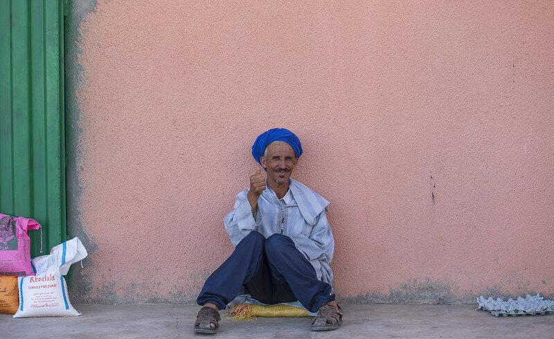 Nkob (Morocco)    Deze vriendelijke man zat heerlijk te genieten in het zonnetje voor zijn snoepwinkel. Toen ik vroeg of ik een foto mocht maken stak hij gelijk zijn duim omhoog. Iets wat (in mijn ervaring) niet gebruikelijk is in Marokko. De meeste mensen willen liever niet op de foto gezet worden. Na het nemen van de foto kocht ik voor 6 Dirham (omgerekend ongeveer 55 cent) een aantal koekjes bij deze man, die ik later uitdeelde aan een paar kinderen, die overigens niet op de foto wilden.