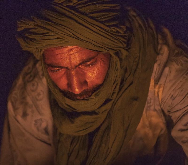 Sahara - Erg Chegaga (Morocco) [❍] ⇢  200 mm - F4 - 1/160 sec - ISO 12800 - No filter   Fotograferen bij extreem weinig licht betekend diafragma naar de grootste opening en ISO omhoog. Dat was ook nodig om deze man te fotograferen in de donkere Sahara met slechts een klein kampvuur als lichtbron.