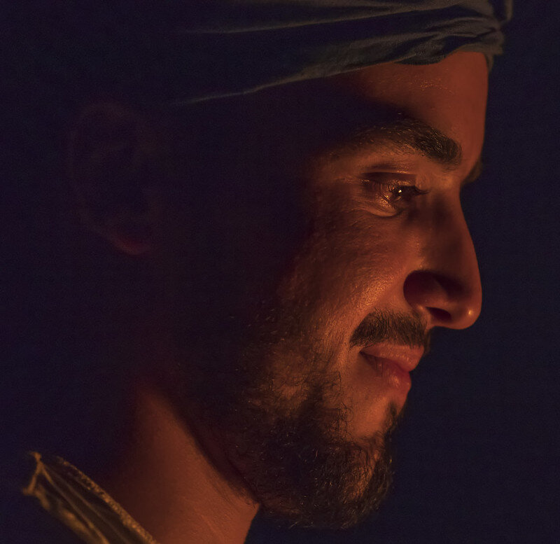 Sahara - Erg Chegaga (Morocco)  Fotograferen bij extreem weinig licht betekend diafragma naar de grootste opening en ISO omhoog. Dat was ook nodig om deze man te fotograferen in de donkere Sahara met slechts een klein kampvuur als lichtbron.