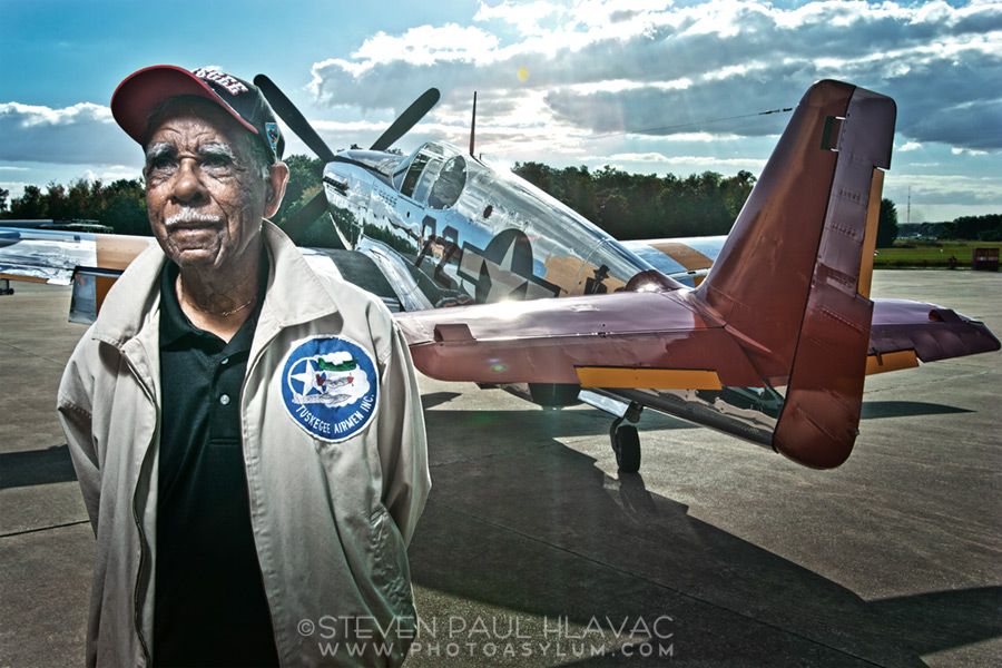 """Clermont, Florida resident and former Tuskegee Airman Daniel Keel poses in front of a restored North American P-51 Mustang fighter bomber (decorated in the infamous """"Red Tail"""" markings) at Fantasy of Flight Air Museum in Polk City, Florida, December 2011. The Tuskegee Airmen flew many types of aircraft in WWII, but are most closely and romantically associated with the """"Red Tail"""" Mustangs. This photo originally ran as part of feature story on Keel in Pulse the Magazine in 2012. ©Steven Paul Hlavac."""