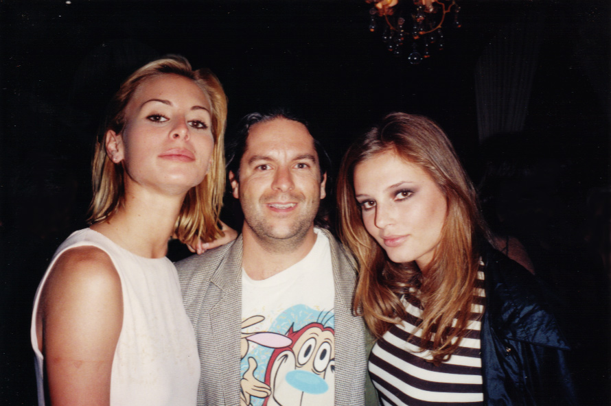 What can I say? Chicks dig Ren & Stimpy! Not that I've ever been one to dwell on the financial end of the business, but at this throw back moment I've got my arms around SEVERAL MILLION DOLLARS worth of fashion merchandise! (L to R): Supermodel Niki Taylor, super shooter Steve Hlavac, supermodel Bridget Hall. Ocean Drive Anniversary Party. Fisher Island, Florida, 1996. Photo ©???