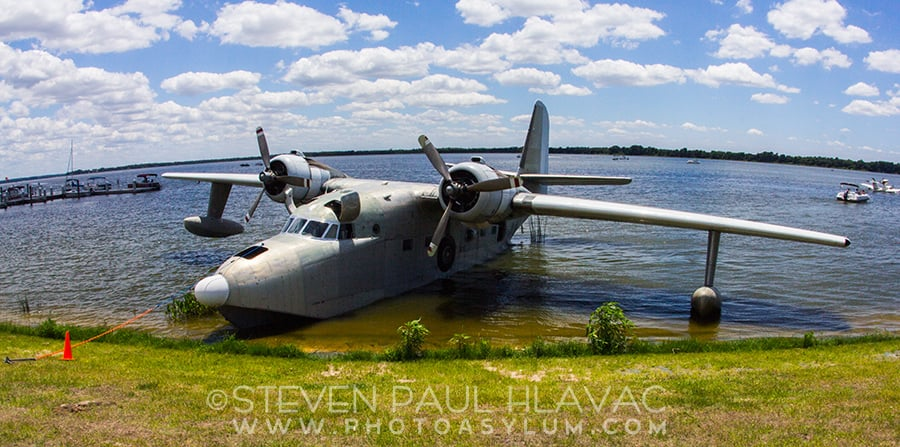 The lovely Grumman HU16 Albatross 'Zeus' seaplane sits docked on Lake Dora for the Tavares Seaplane Fly-In this past May. My wide angle lens belies the massiveness of the aircraft. Her wingspan is 98 feet! ©2015 Steven Paul Hlavac.