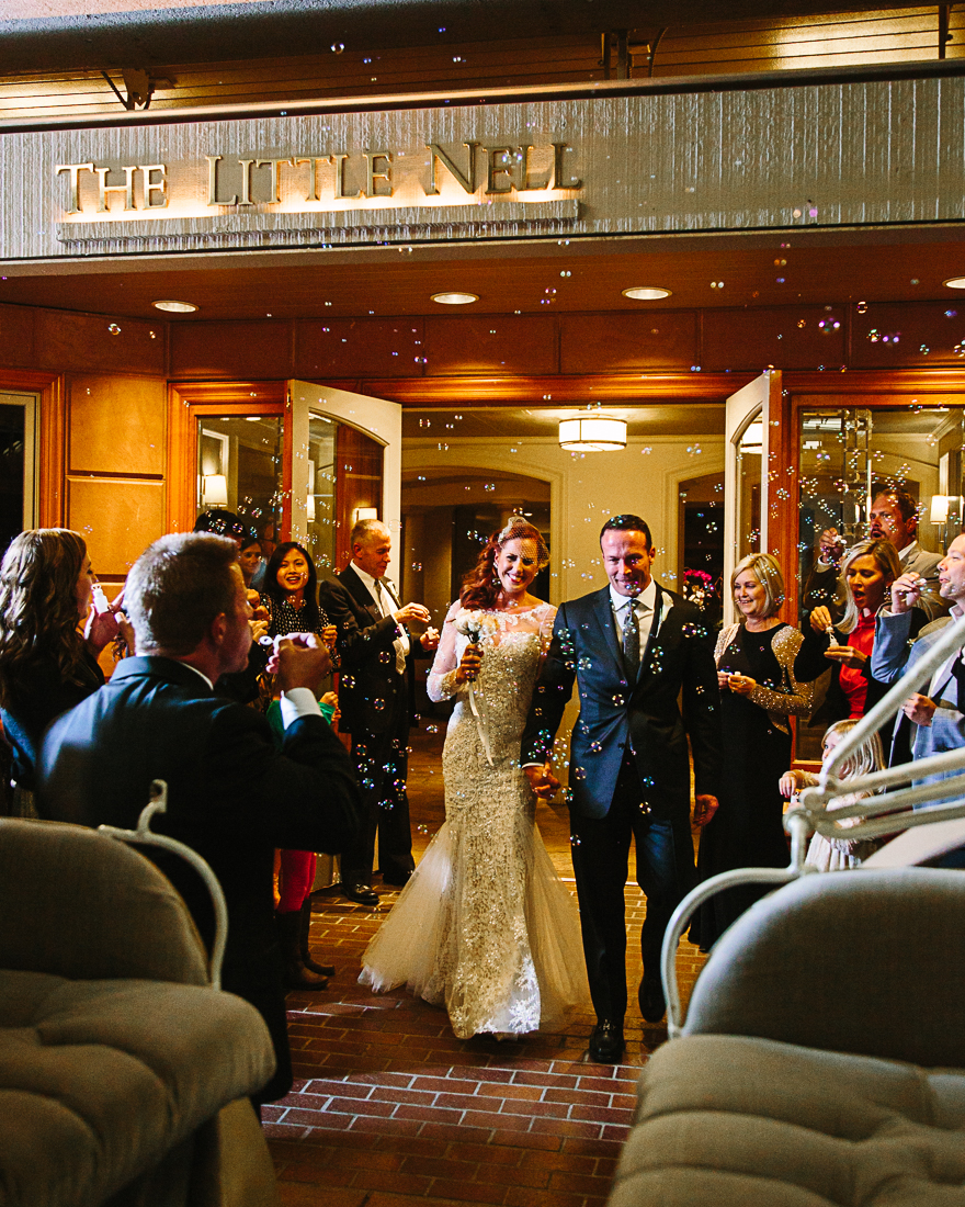 The couple exits to a horse-drawn carriage, a surprise gift from the bride to the groom, after their wedding at The Little Nell in Aspen.