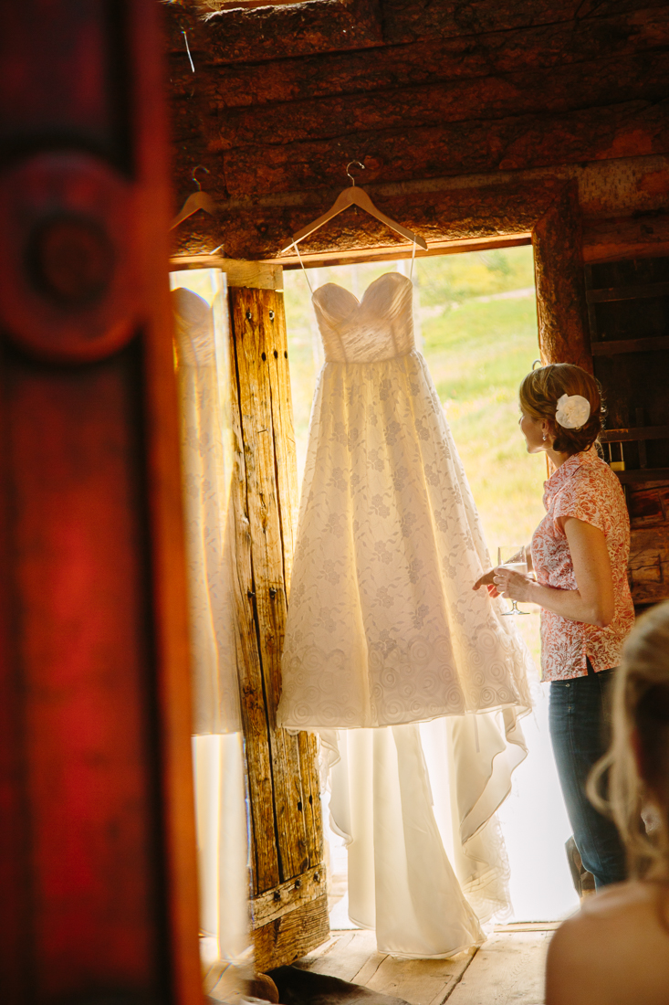 Telluride Wedding Photography | Bride Getting Ready | Wedding Dress Hanging in Doorway at Gorrono Ranch Saloon | Cat Mayer Studio | www.catmayerstudio.com