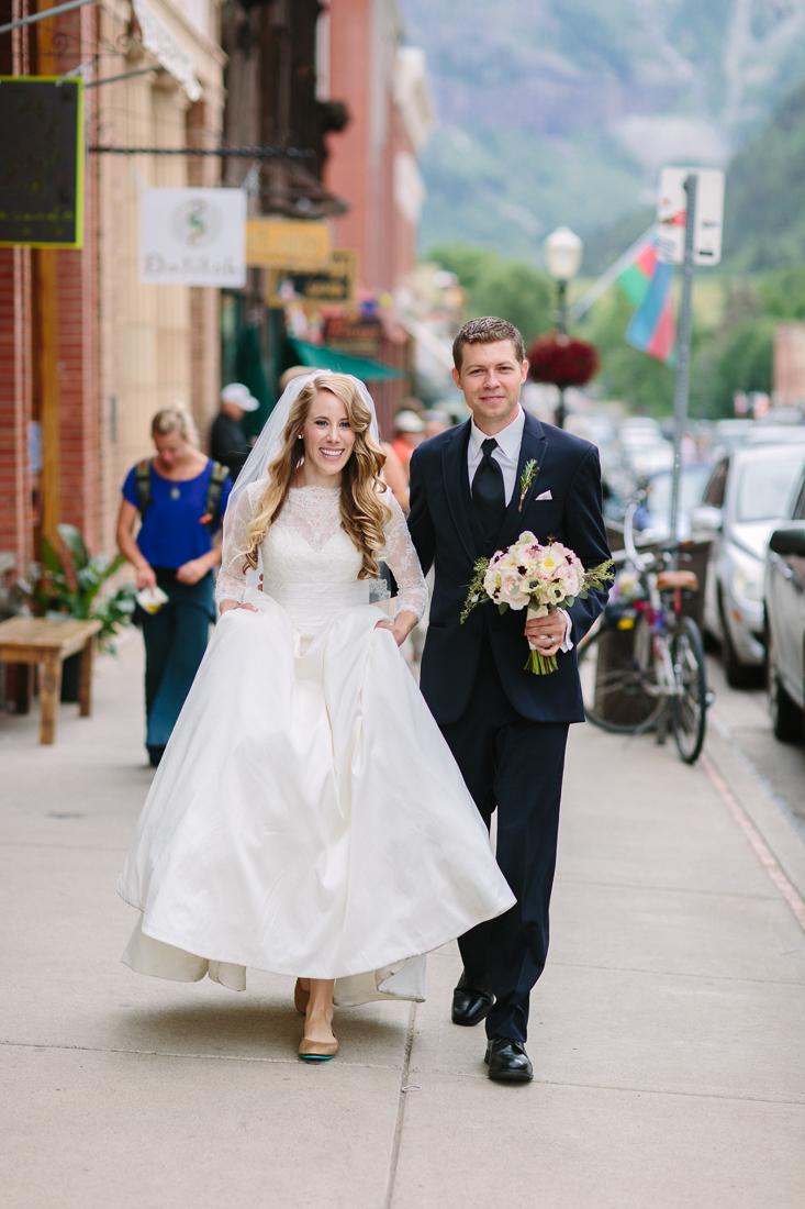 Bride and Groom walking through town after their morning wedding at St. Patrick's Church and before their reception at Allred's.