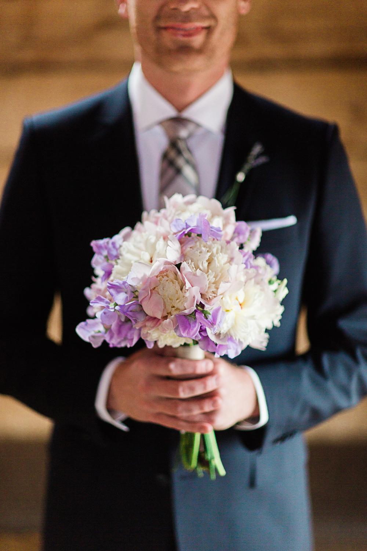 Groom holding Bride's Bouquet