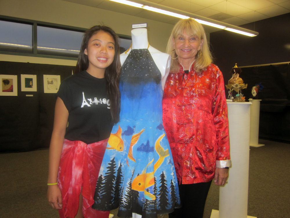 Norwalk High senior Donatie Santos and AP fashion and art teacher Jacque Fabritz with Santos' painted dress.