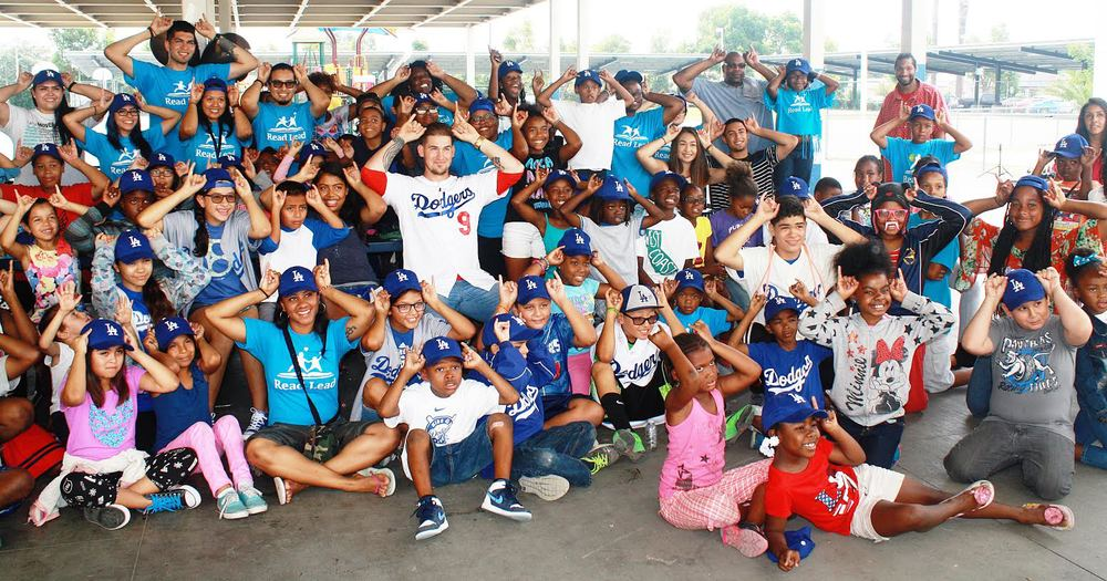 "More than 100 students at Lynwood Unified's Helen Keller Elementary School sit with Dodgers catcher Yasmani Grandal on Friday, July 31. The students are all posing with horns in honor of Grandal who is nicknamed ""Tasmanian Devil."""