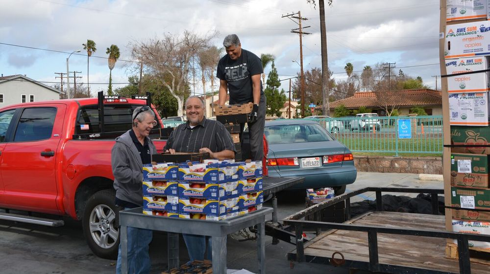 FoodHelp founder Bob Varden (left) helping to unload truck with Mark Schoch and Mike Colacion. Photo by Carol Kearns