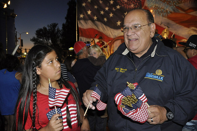 Norwalk mayor Mike Mendez distributes American flags at a July 4 fireworks show last year. Photo courtesy city of Norwalk