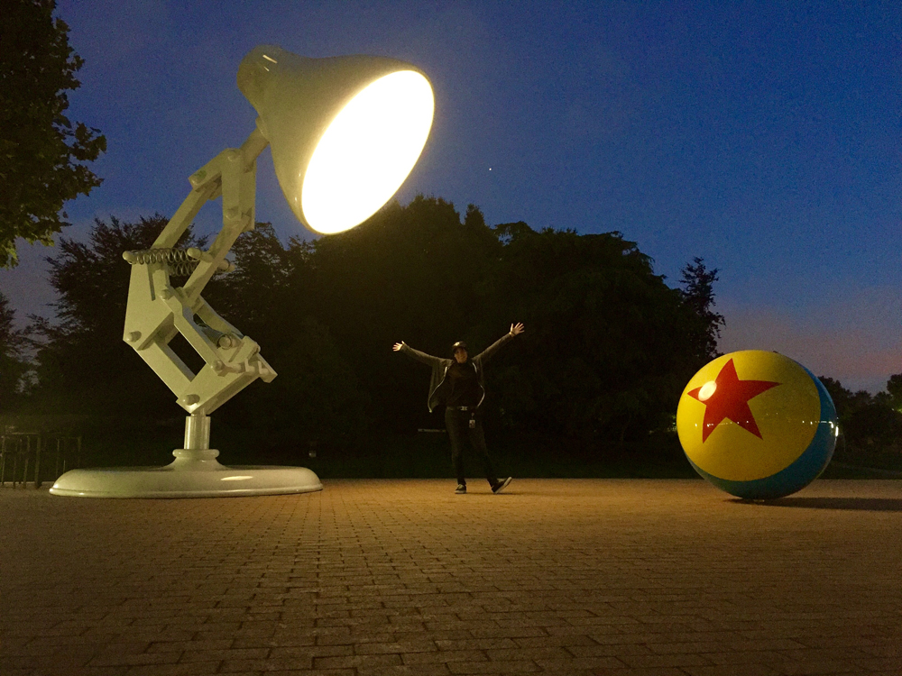 Briana Ornelas takes a break from working in the studio to snap a picture with the giant versions of the iconic Pixar luxo lamp and 4 foot rubber ball located in front of the main building on the Pixar Studio lot.
