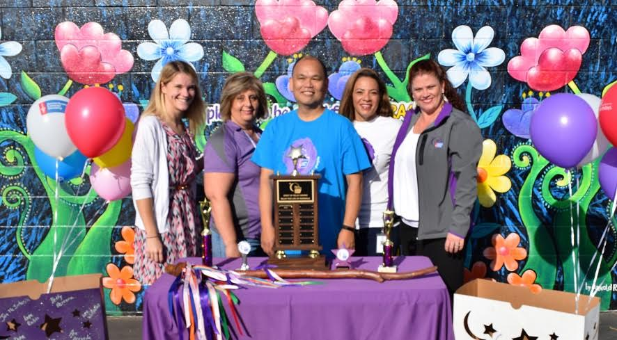 American Cancer Society representatives presented Johnston Elementary School first-grade teacher Dan Calma, center, with a Spirit of Relay award Sept. 23 at the school's flag ceremony.
