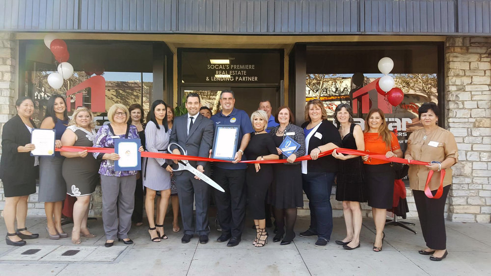Carlos Martinez (holding scissors) at a ribbon-cutting ceremony last week for his new Downey real estate office.
