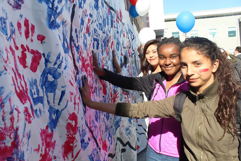 Firebaugh High freshmen (from left) Kassandra Ortiz, Deirra Hickson and Leslie Macias stamp their handprints upon a map of the United States during a Nov. 18 unity rally in Falcon Square.
