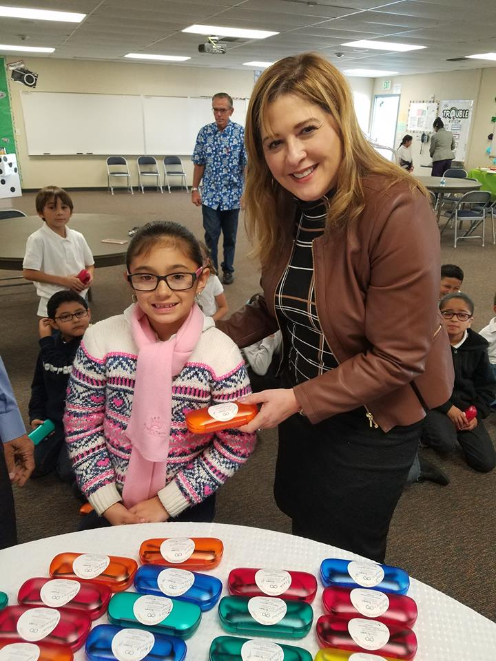 Paramount Superintendent Ruth Pérez stands with a student receiving a new pair of eyeglasses. Nearly 100 Los Cerritos School students were provided new eyeglasses through a partnership with nonprofit Vision To Learn.