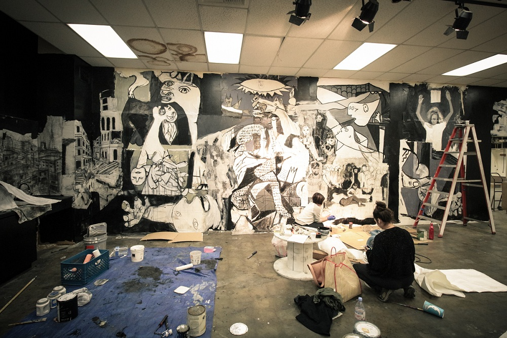 "Pati Lomeli and Romina Del Castillo from Long Beach-based art collective FA4 work on their modern interpretation of Picasso's ""Guernica"" for the 2017 FAR Bazaar at Cerritos College this weekend. Photos 