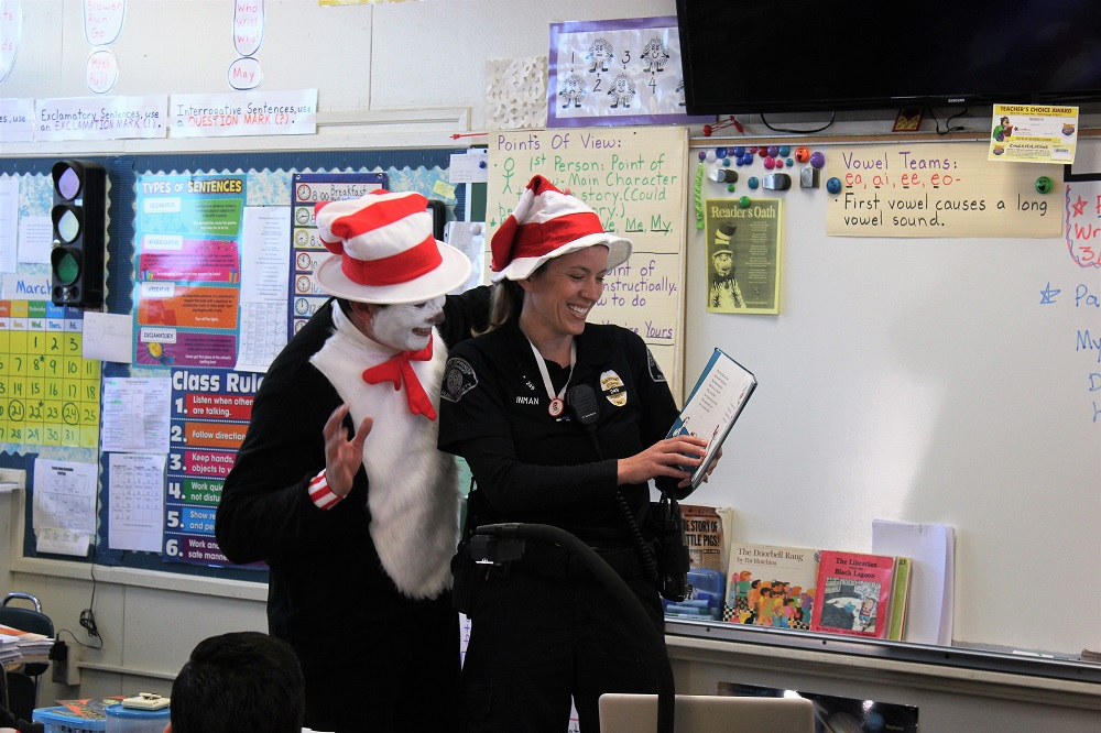 "Whittier Police Officer Lindsay Inman reads to a class of Rancho Santa Gertrudes Elementary School students with principal Octavio Perez, dressed as ""The Cat in The Hat,"" lurking behind."