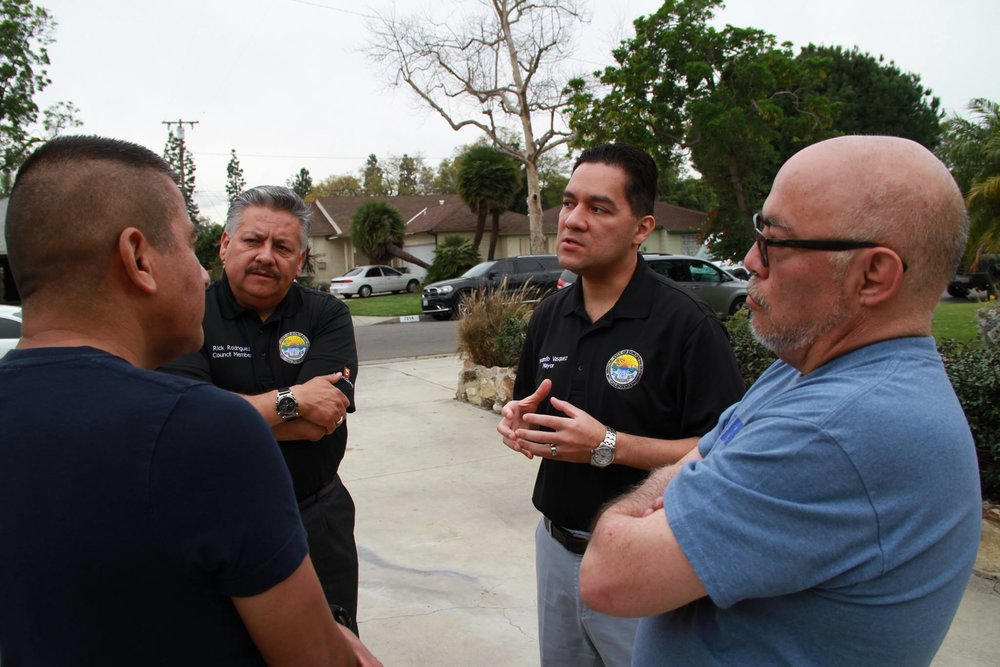 Councilman Rick Rodriguez and Mayor Fernando Vasquez speak to residents of a Neighborhood Watch group. Photo by Hans Fritz