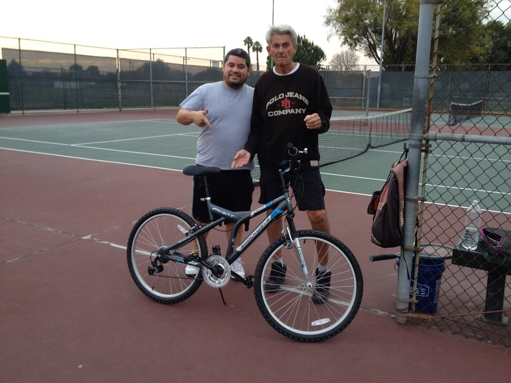 Jerry Baxter, right, with tennis partner Jose Perez at Furman Park. Perez and Larry Christon presented Baxter with a new bike as a Christmas present.