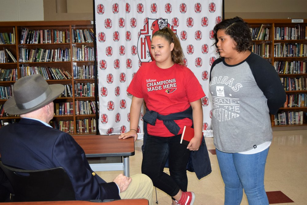 Two Whittier High School students stop to talk to William C. Gordon, a 1955 grad who returned to his alma mater to tell his story of perseverance and the importance of giving back to the community on Sept. 8.