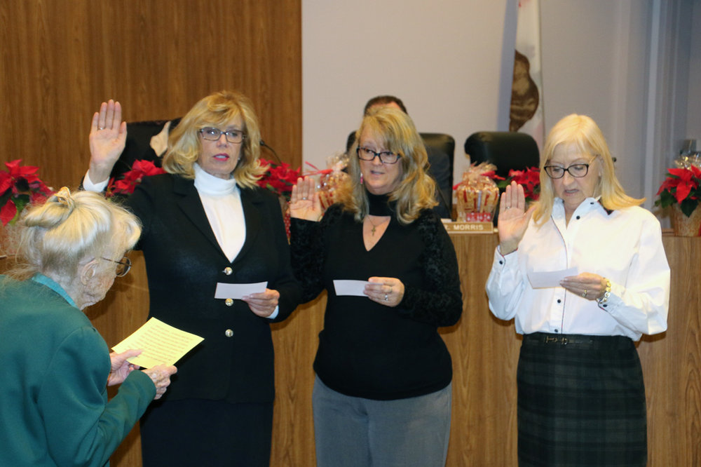 Dr. Mary Stauffer administers the oath of office to school board members Martha Sodetani, Nancy Swenson and Barbara Samperi. Photo by Alex Dominguez