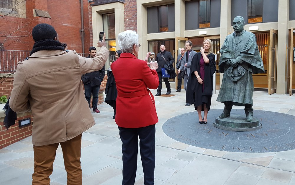 Graduate Alexandra MacGregor getting her picture taken next to King's statue by grandmother and friend. Photo by Carol Kearns