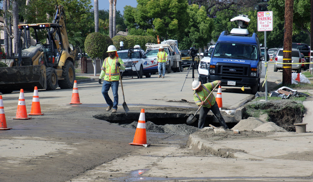 Public Works crews fill in a sinkhole on Rives Avenue Monday. Photos by Alex Dominguez