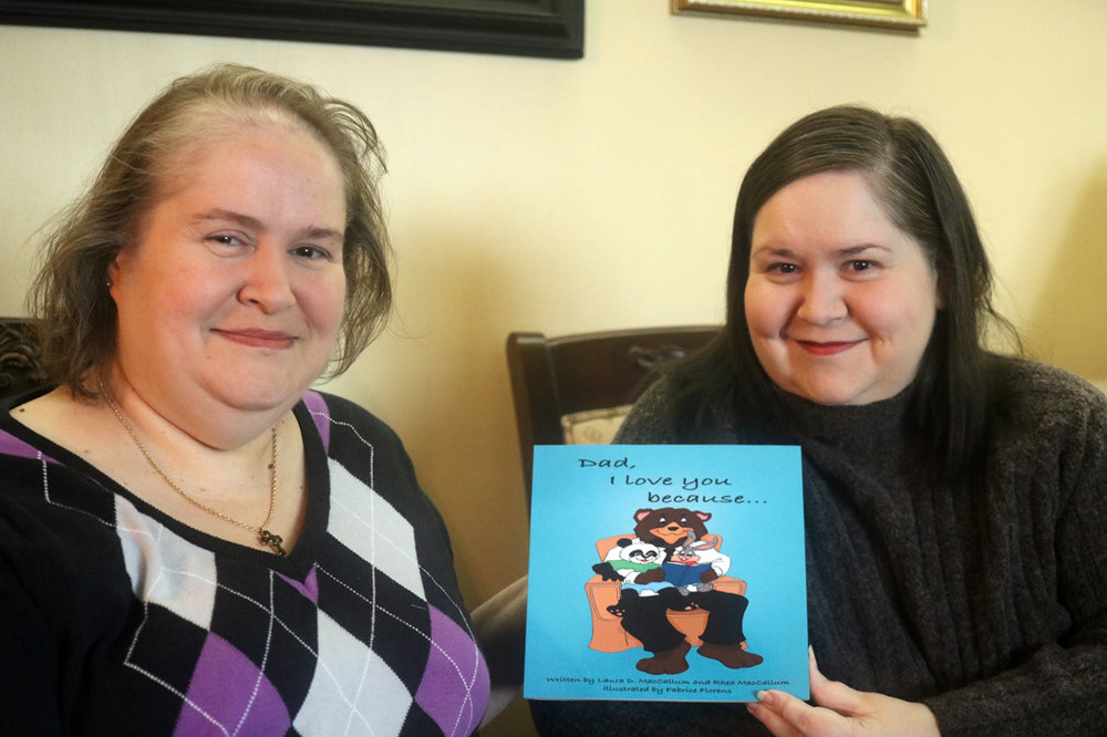 """Laura and Rhea MacCallum with their book, """"Dad, I Love You Because…"""" Photo by Alex Dominguez"""