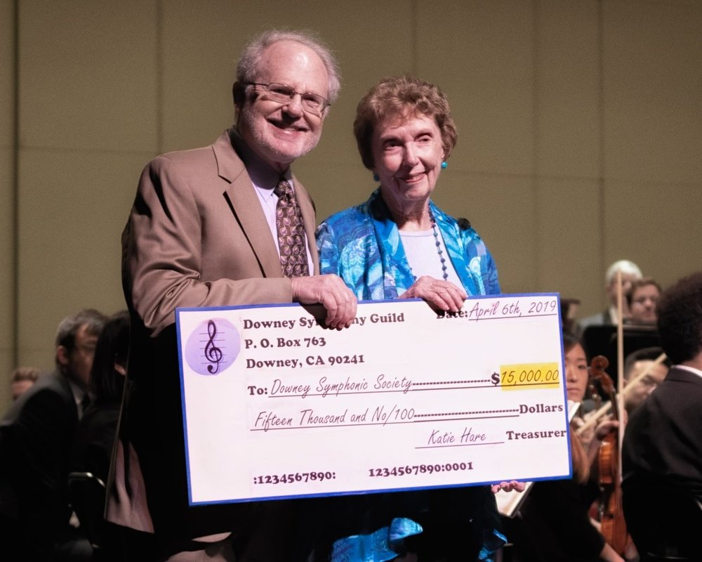 Marge Lewis, membership chairman of the Downey Symphony Guild, presents a $15,000 donation to Don Marshall, president of the Downey Symphonic Society, on April 6, on the stage of the Downey Theatre during the Downey Symphony Orchestra's Gershwin concert. Photo courtesy Downey Symphony Guild