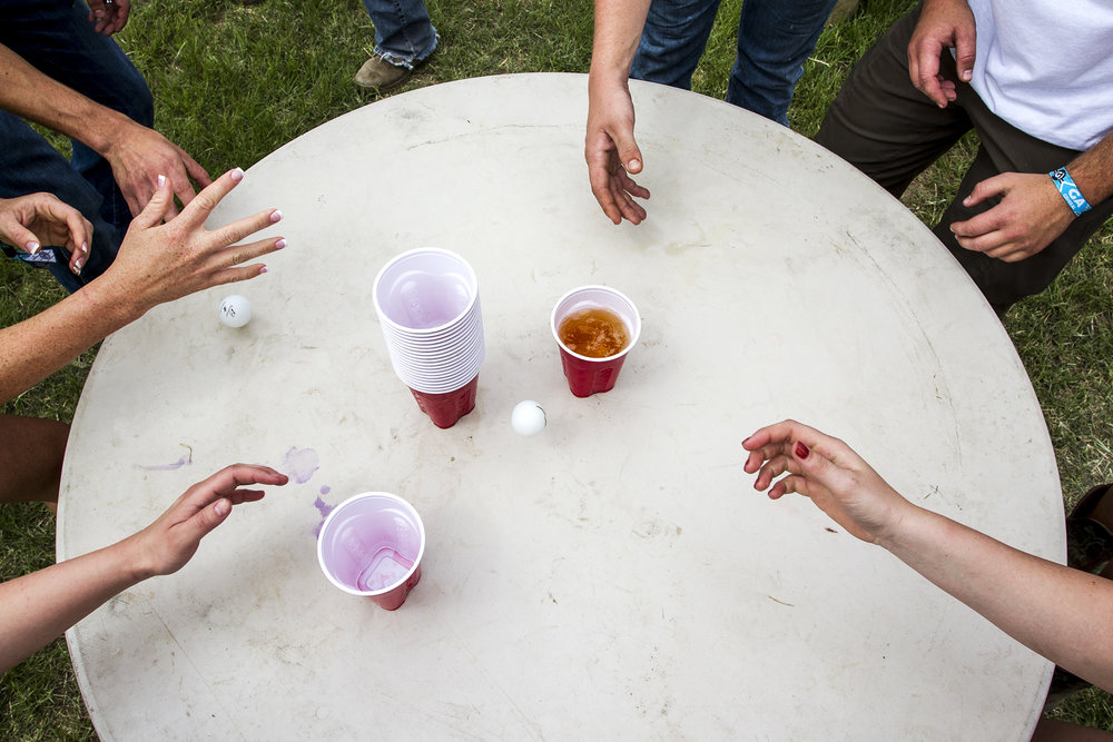 Festival-goers play a drinking game at a campsite during Country Thunder in Florence, Ariz.