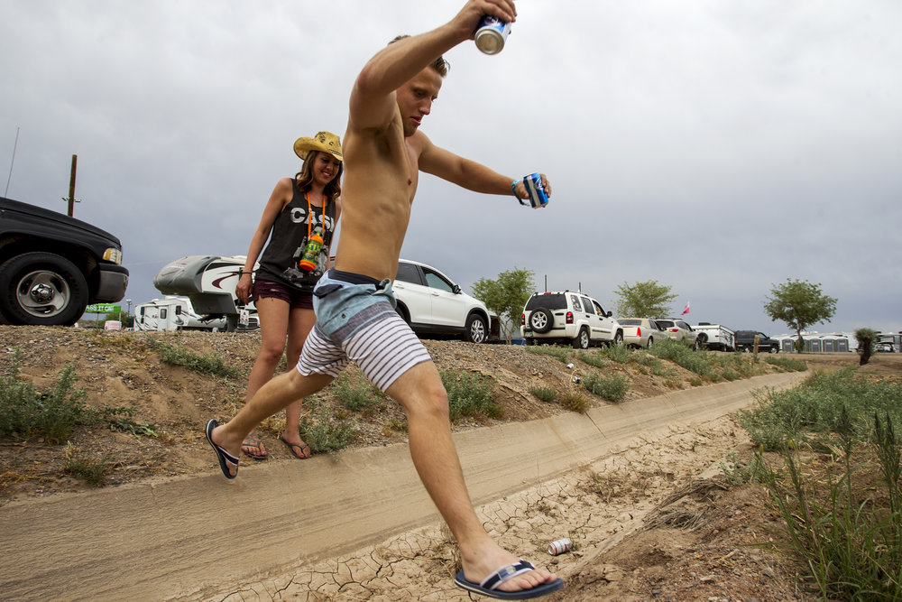 Michelle Block and Albrim Aliu jump over a ditch at a camping area during Country Thunder in Florence, Ariz.