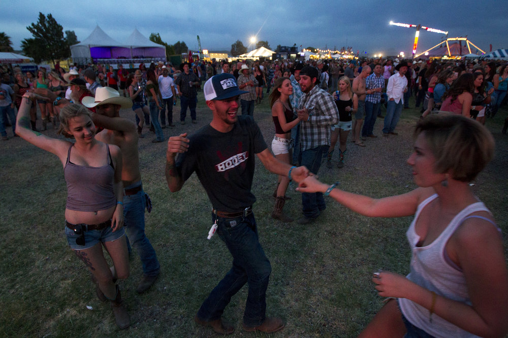 Festival-goers dance while Chase Bryant performs during Country Thunder in Florence, Ariz.