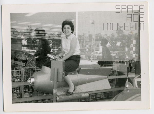 Woman on Coin-Op Rocketship in Front of Grocery Store (circa 1955)