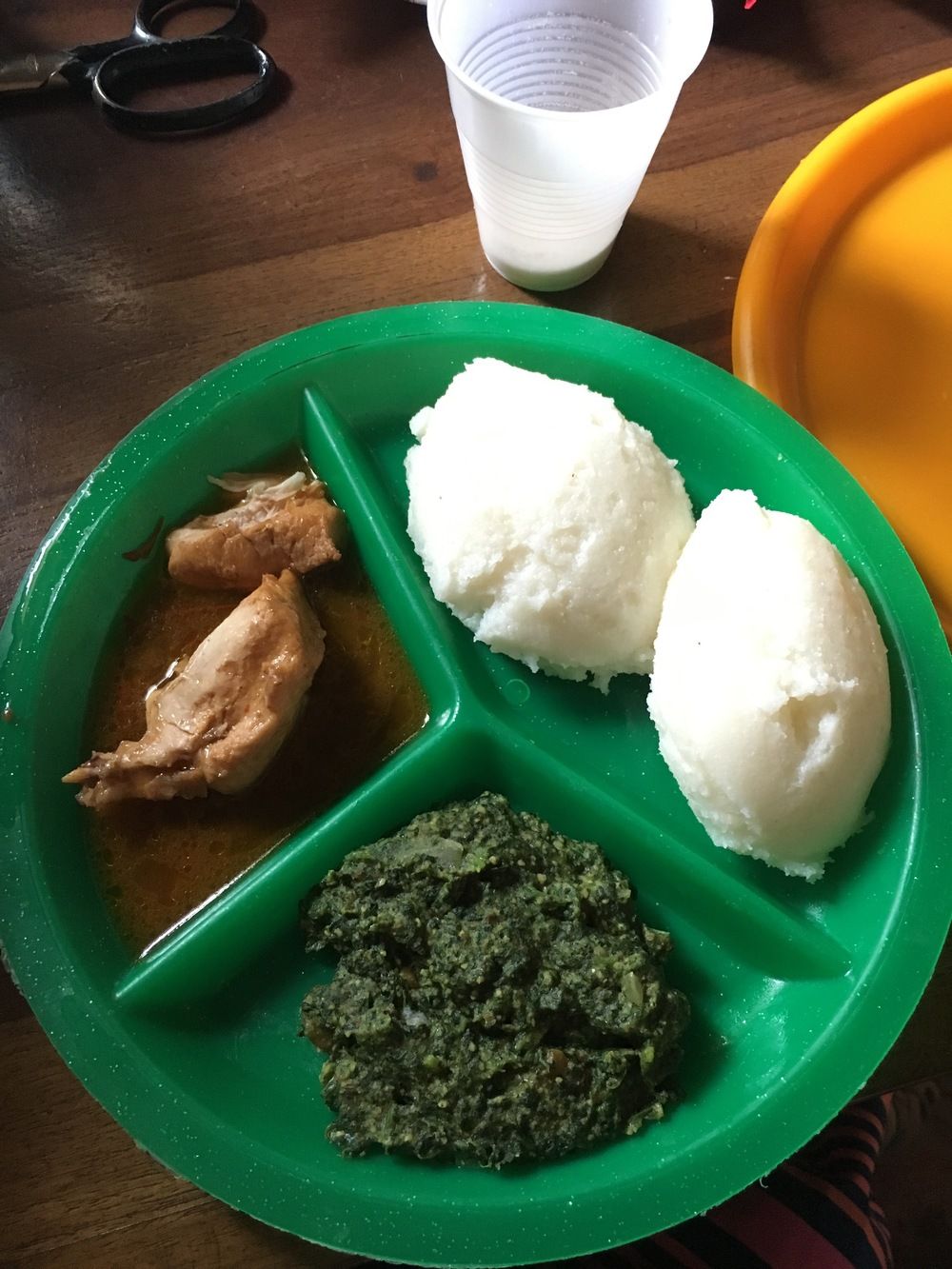 "1pm and lunch is served! This is typically the biggest meal of the day. The top right is Nshima- a corn meal mixture thicker than grits. It is balled up in the right hand and used to eat the ""relish"" or stew (bottom is stewed pumpkin leaves called Chibwabwa), and the meat with sauce (chicken here)."