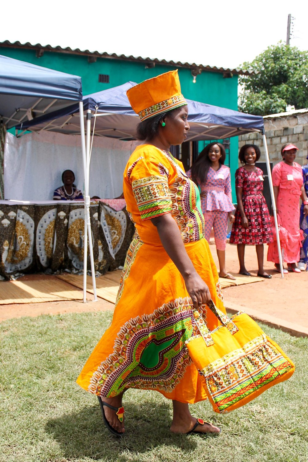 Gladys' head-to-toe ensemble gets quite the reaction from the crowd. Matching purse, a-line dress, and traditional hat in a beautiful traditional chitenge fabric.