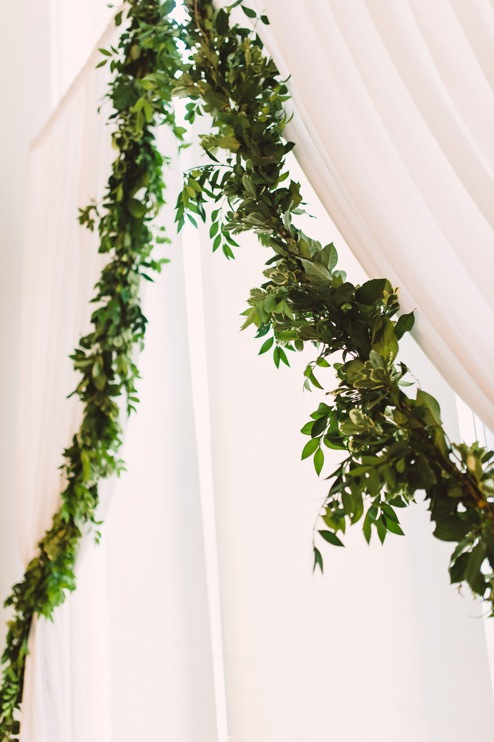 Wedding ceremony in the Atrium at the Mint Museum, Wedding draping, Wedding arch, Greenery garland, Wedding ceremony decor, Wedding ceremony set-up, Mint Museum Uptown wedding in Charlotte, North Carolina by The Graceful Host