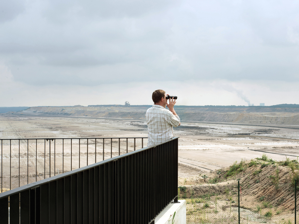 "Outlook Platform  Observation points and towers were built to allow tourists to have views over the active mines and the changing landscape. Here, visitors are gazing from an outlook platform at the scale of the open cast mine ""Nochten""."
