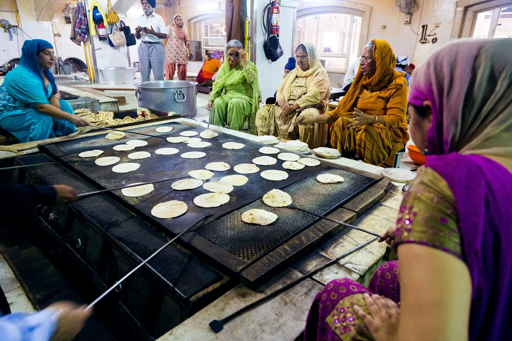 A group of women cook and flip  chapati  that will be used to feed the hungry.  These women are just a few of the volunteers that help feed over 10,000 poor and homeless people a day at the Sikh Temple Gurudwara Bangla Sahib in New Delhi, India.