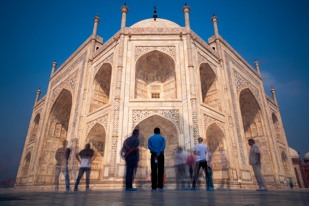 A man stands in admiration of the Taj Mahal as others come and go.