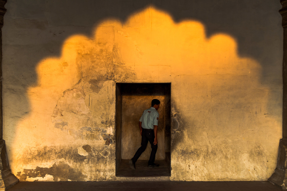 A security guard walks through a doorway as the sun sets at the Red Fort in Agra, India.