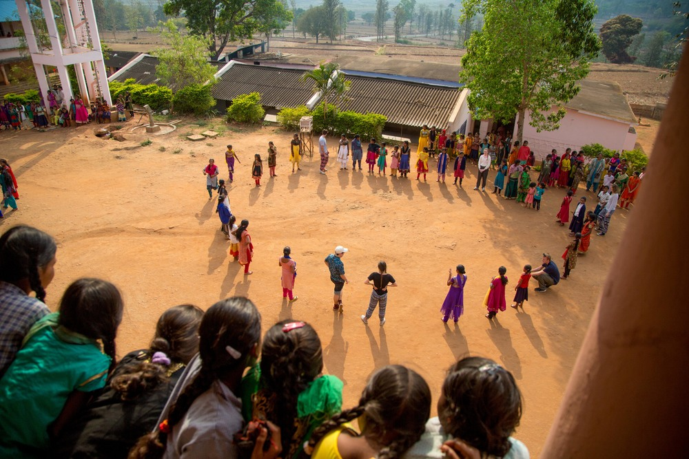 "A group of girls watch as a game of ""duck, duck, goose"" is played in the court yard of a government funded all girls boarding school in the Araku Valley tribal area."