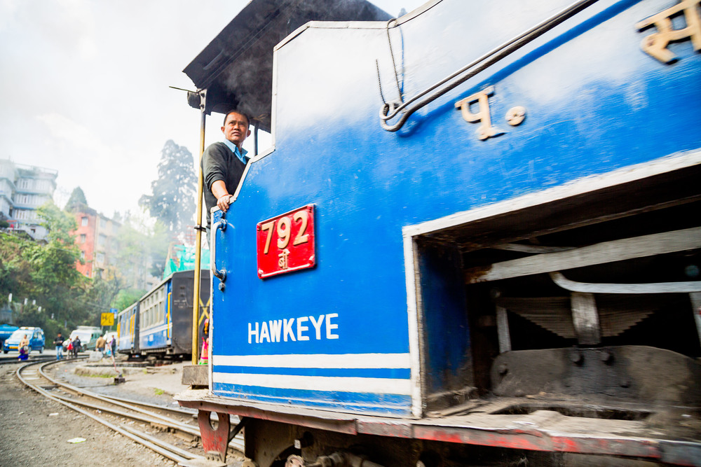 """The conductor of the """"Toy Train"""" looks out as he pulls into the station."""