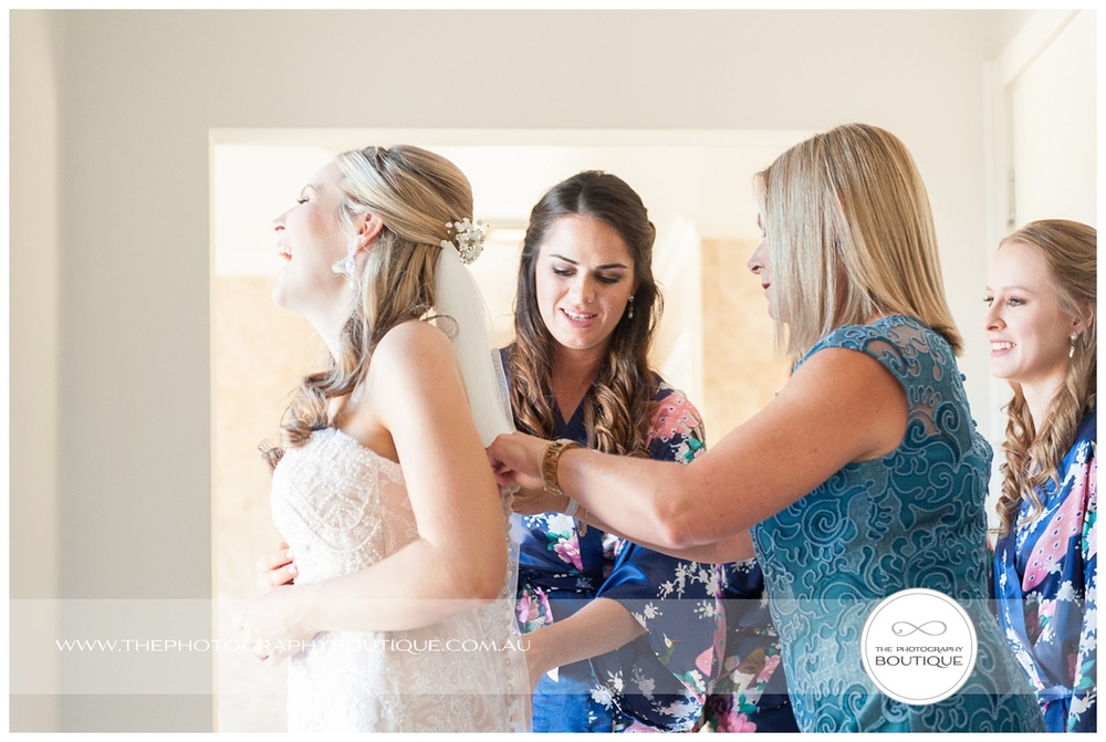 mum helping bride put wedding dress on