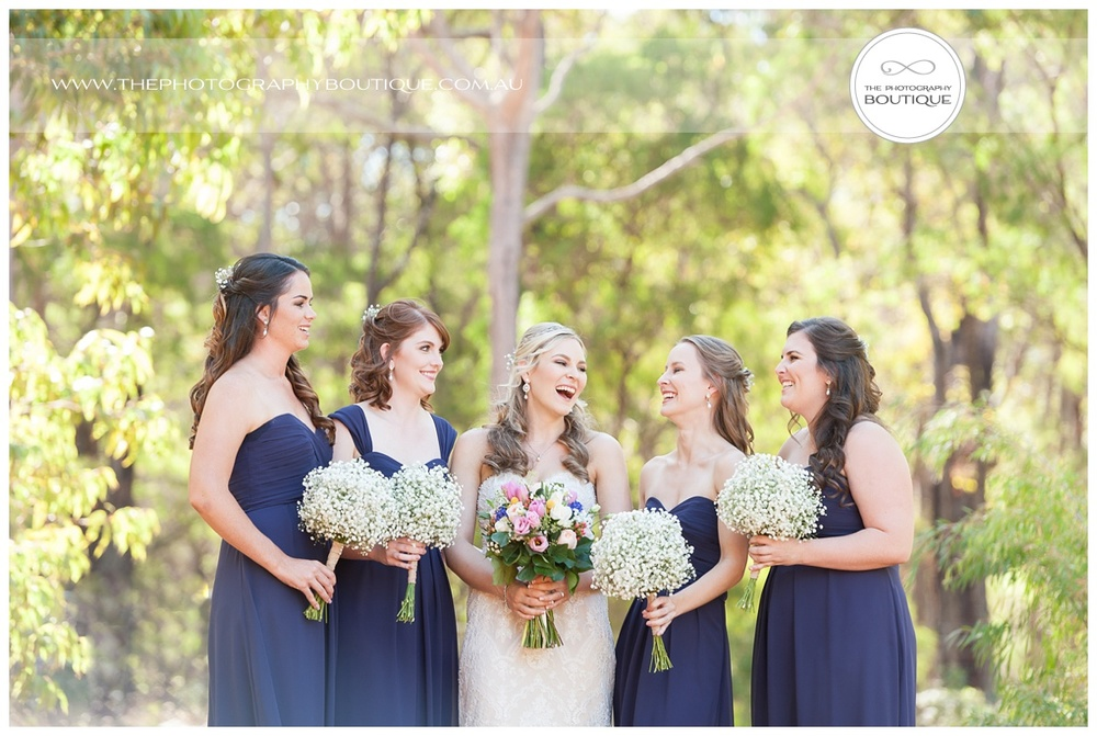 bride laughing with bridesmaids in bush setting